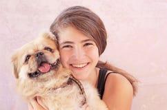 有pekingese狗的青少年的女孩 免版税库存图片