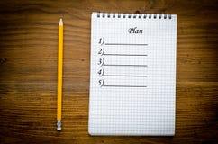 有pencile的黑笔记本在木背景 免版税图库摄影