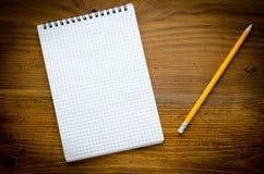 有pencile的黑笔记本在木背景 库存图片