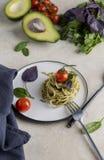 有pesto、草本和西红柿的意大利意粉在白色板材 库存照片