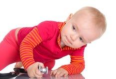 有phonendoscope的小婴孩坐白色背景 库存图片