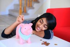 有Piggybank和硬币的美丽的印第安女孩 免版税库存照片
