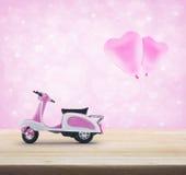 有pinkl心脏爱气球的桃红色滑行车玩具在木桌o上 库存图片
