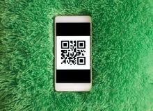 有qr代码的手机在屏幕上 人为软的休息背景 免版税库存图片