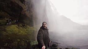 有selfie棍子摄制的年轻旅游人在gopro照相机强有力的瀑布Seljalandsfoss在冰岛在阴暗天 股票录像