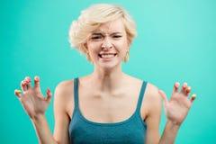 有shorwing她的sarp钉子的短的公平的头发的愤怒,疯狂,被激怒的女孩 库存照片