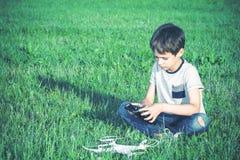 有sittting在草的寄生虫的男孩 图库摄影