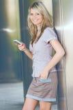 有smartphone微笑表面纵向的愉快的妇女 图库摄影