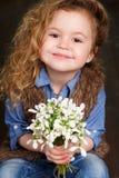 有snowdrops大花束的美丽的小女孩  免版税库存图片