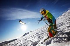 有snowkite的愉快的挡雪板在随风飘飞的雪站立 库存照片
