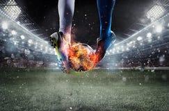 有soccerball的足球运动员在体育场的火在比赛期间 免版税库存照片