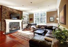 有stobe壁炉和皮革沙发的豪华客厅。 免版税库存图片