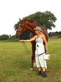 有strav帽子吃草的主角马的妇女 免版税库存照片