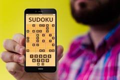有sudoku的app行家智能手机在屏幕上 库存照片