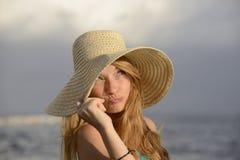 有sunhat的白肤金发的妇女在海滩 免版税库存图片