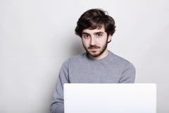 有sylish黑发的英俊的有胡子的人穿偶然灰色毛线衣检查在膝上型计算机的电子邮件,使用自由无线互联网骗局 免版税库存照片