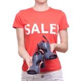 有T恤杉的妇女有题字销售手中女性鞋店购买折扣的 免版税图库摄影