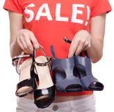 有T恤杉的妇女有题字销售手中女性鞋店购买折扣的 图库摄影
