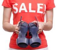 有T恤杉的妇女有题字销售手中女性鞋店购买折扣的 免版税库存照片