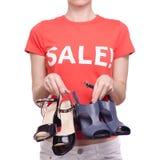有T恤杉的妇女有题字销售手中女性鞋店购买折扣的 库存图片