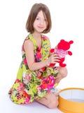 有teddybear她的红色的可爱的小女孩。 库存照片