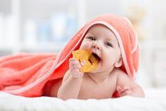 有teether的逗人喜爱的婴孩在浴以后的一块戴头巾毛巾下 免版税库存图片