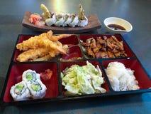 有teriyaki鸡米加利福尼亚寿司卷的Bento箱子 免版税图库摄影