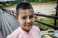 有thanaka粉末的未认出的年轻亚裔男孩在面孔 库存图片