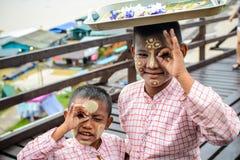 有thanaka粉末的未认出的年轻亚裔男孩在面孔 图库摄影