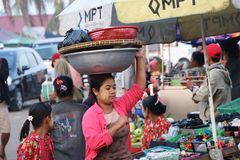 有thanakha缅甸粉末的Myanmese妇女在她的面孔在她的头上把大铝上釉的水池放给带来产品 库存照片