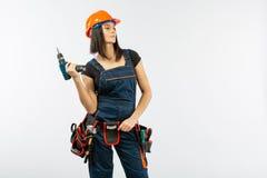 有toolbelt的少妇使用driil和为她的一些电动工具在家工作 工作在平改造的女孩 大厦,修理 免版税图库摄影