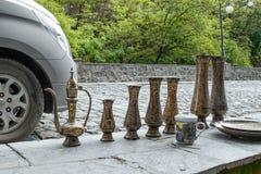 有tradiitional装饰品的传统东方黄铜手工制造水罐由一个摊贩的待售旧货市场的在Sheki: 免版税图库摄影