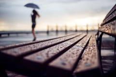 有umbrela的湿长凳和剪影妇女 多雨天气概念 库存照片