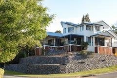 有underporch和许多的现代Queenslander房子室外生存空间-在与相当蓝色瓦屋顶的小山 库存图片