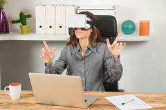 有vr耳机和膝上型计算机的女实业家在工作场所 免版税库存图片