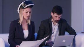 有VR耳机和膝上型计算机的谈论两个的商人工程项目 免版税库存图片