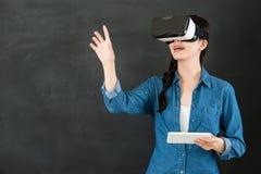 有VR耳机数字式片剂的亚洲学生触摸屏 库存照片