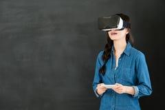 有VR耳机智能手机的亚洲学生触摸屏 库存图片