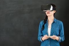 有VR耳机智能手机的亚洲学生触摸屏 图库摄影