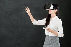 有VR耳机智能手机的亚洲老师触摸屏 库存照片