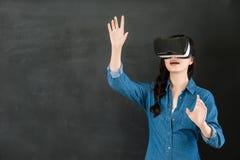 有VR耳机的亚洲女学生控制屏幕 免版税库存照片