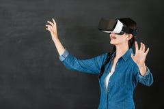 有VR耳机的亚洲女学生控制屏幕 库存图片