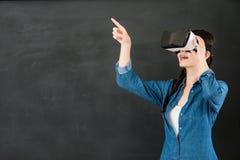 有VR耳机的亚洲女学生触摸屏 免版税库存图片