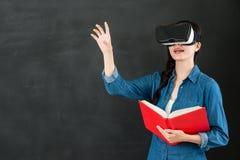 有VR耳机的亚洲女学生触摸屏 免版税图库摄影