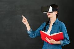 有VR耳机的亚洲女学生触摸屏 库存照片