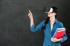 有VR耳机的亚洲女学生触摸屏 库存图片