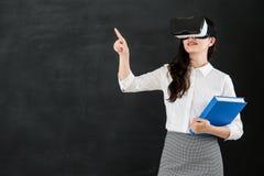 有VR耳机的亚洲妇女老师触摸屏 库存照片