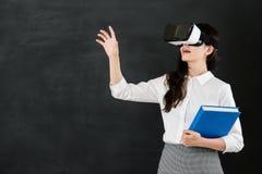 有VR耳机的亚洲妇女老师触摸屏 图库摄影