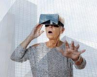 有VR虚拟现实耳机的资深妇女震惊 库存照片