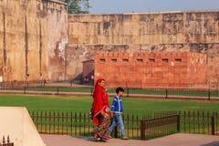 有waling在阿格拉堡,北方邦,印度附近的男孩的妇女 免版税库存图片